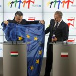 Prime Minister of Hungary Victor Orban, left, hands the European Union flag to Poland's Prime Minister Donald Tusk, right, in a symbolic gesture of handing over the union's rotating presidency in Warsaw, Poland on Friday, July 1, 2011. (AP Photo/Czarek Sokolowski)